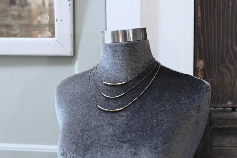 "Bust wearing three ""London"" brass bar necklaces each at a different length. The lengths measure 15 inches, 18 inches, and 21 inches."