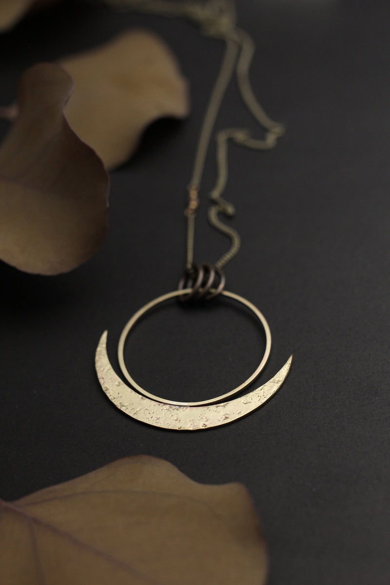 "Close up of CIVAL Collective's ""Lark"" cast brass necklace on black background, the necklace has a large open circle with a textured crescent moon cradling it from below."