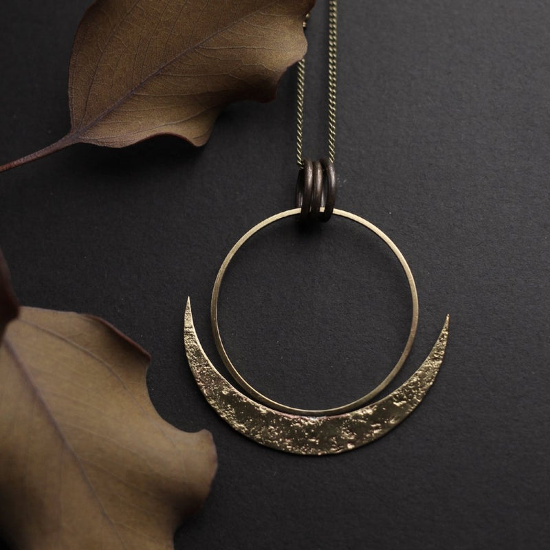 "Close up of ""Lark"" cast brass necklace that has a large open circle with textured crescent moon cradling it from below."