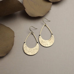 "Close up of Cival's ""Loral"" earrings, they are hand textured half moons stitched onto open teardrop shape brass rings."