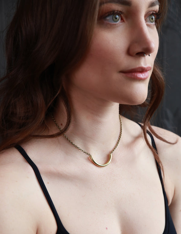 Beautiful woman modeling brass necklace handmade by Milwaukee's most loved jewelry designers, Cival Collective.