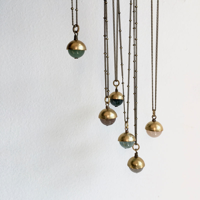 "Six ""Coco"" necklaces hanging together against a white background, each necklace has a different round stone with brass cap pendant."