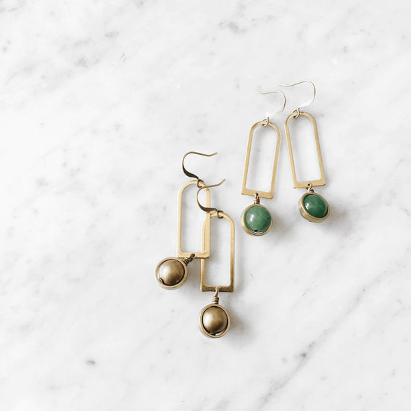 Two modern brass arch earrings with brass saddle set stones at bottom of each arch, one pair in jade & one in smokey quartz.