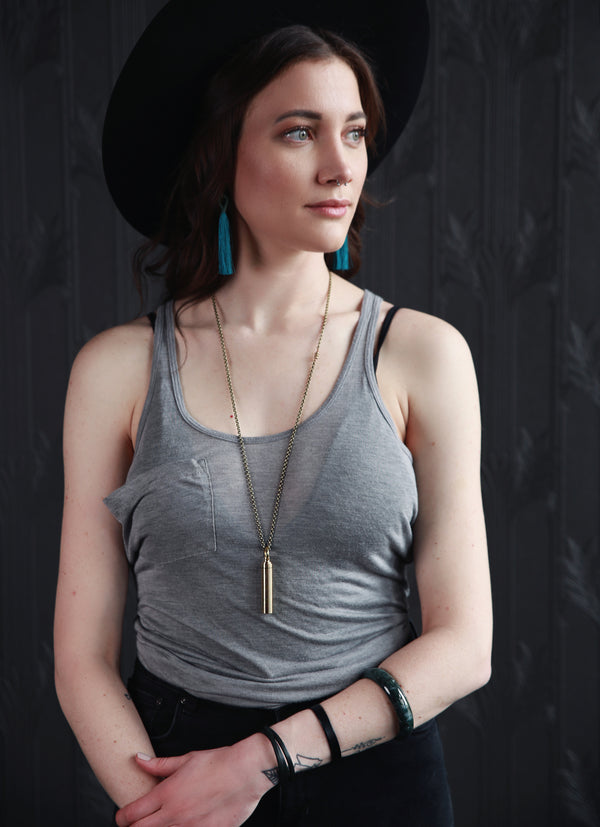 Female modeling earrings, necklace, and bracelets crafted by local Milwaukee Jewelry Designers, Cival Collective.