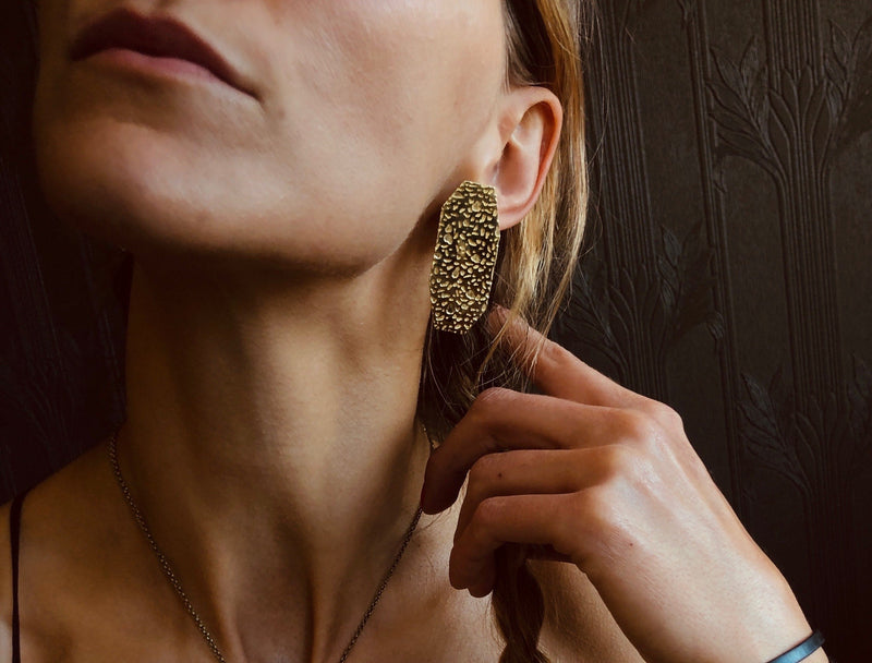 Model wearing brass geometric, gem inspired & organic texture stud statement earrings by CIVAL Collective.