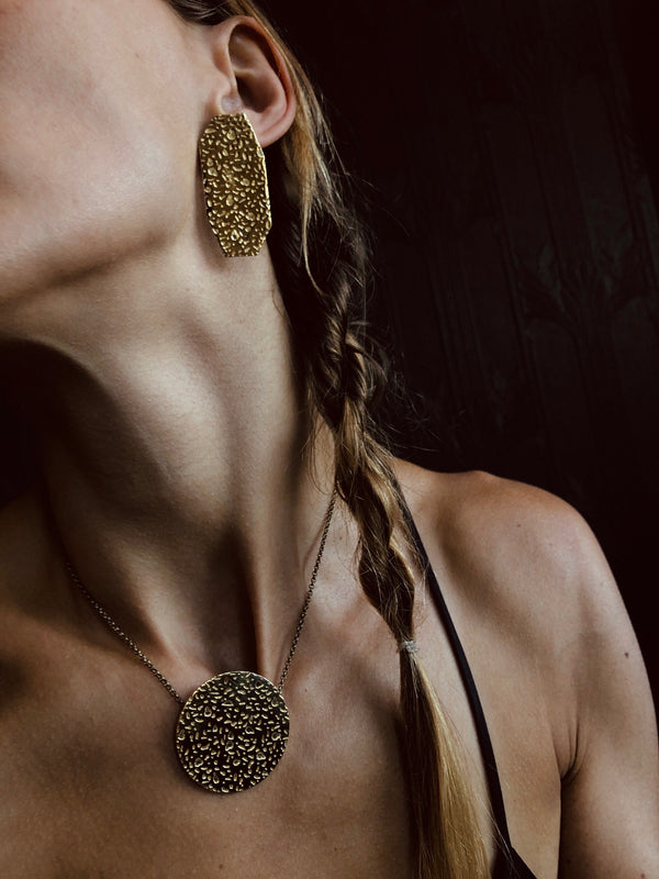 Model wearing geometric brass textured earrings and large textured brass circle necklace that sits just below choker length.