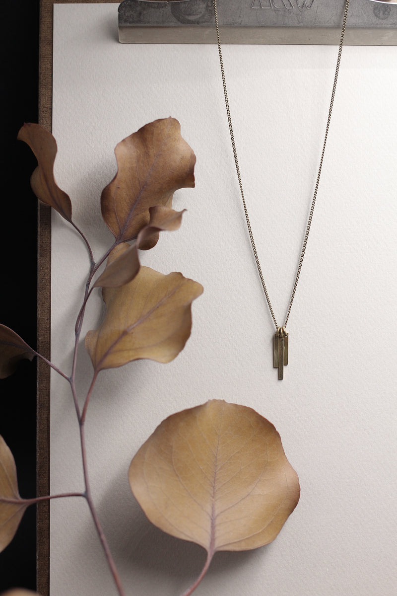 """River"" necklace that has 3 brass tabs hanging in waterfall sequence on brass chain and displayed hanging on white background with brown leaves next to it."