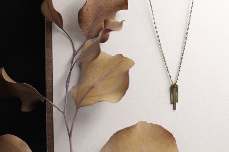 Dainty brass tab fringe necklace with 3 tabs on chain in waterfall cascade orientation.