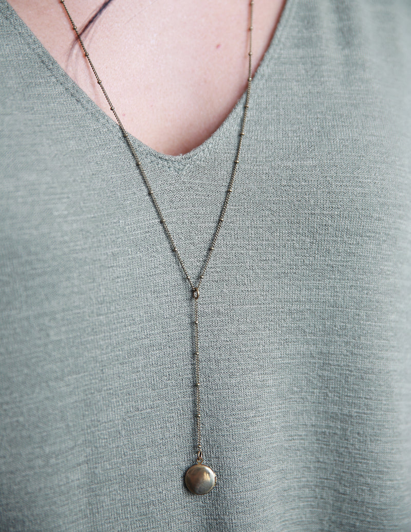"CIVAL Collective's ""Vie"" rosary style necklace on model that is 24 inches long and has a 2 inch drop with little brass locket at the end."