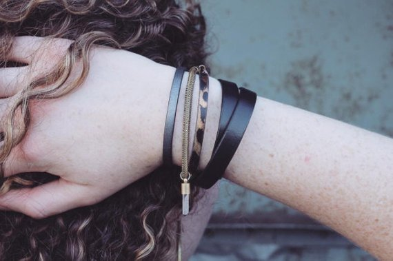 Model wearing black leather 10mm wide double wrap bracelet on wrist with other leather bracelets all made by CIVAL Collective.