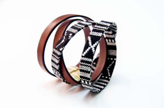 "CIVAL's ""Acer"" bracelets shown in tan Italian leather and black & white ""IKAT"" fabric, both 10mm wide and double wrapped and closed with magnetic clasp."