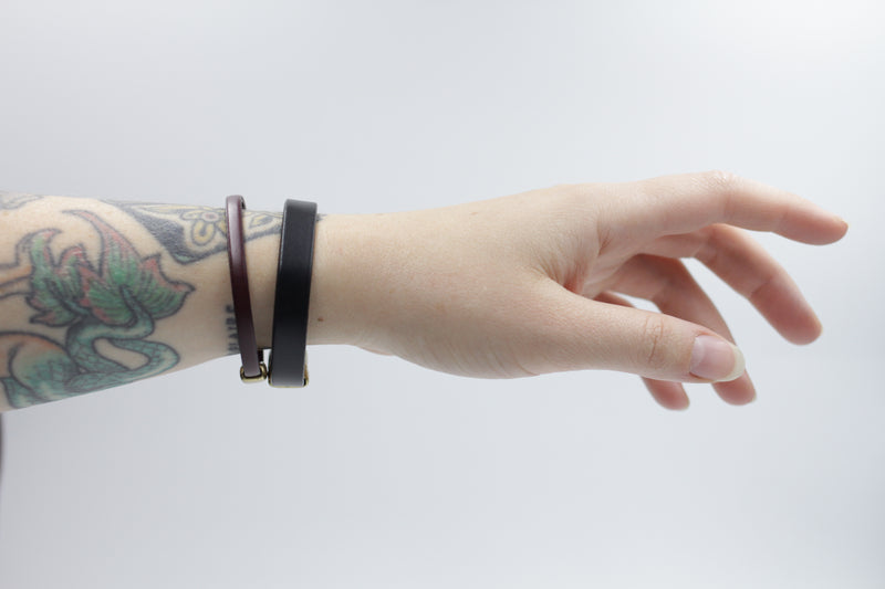 "CIVAL Collective's ""Aime"" bracelet in mahogany leather and ""Acer""  bracelet in black leather layered together on model's wrist."