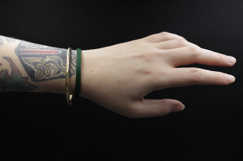 "CIVAL Collective's ""Aime"" bracelet in bottle green leather displayed on model's wrist and layered with textured brass bangle."