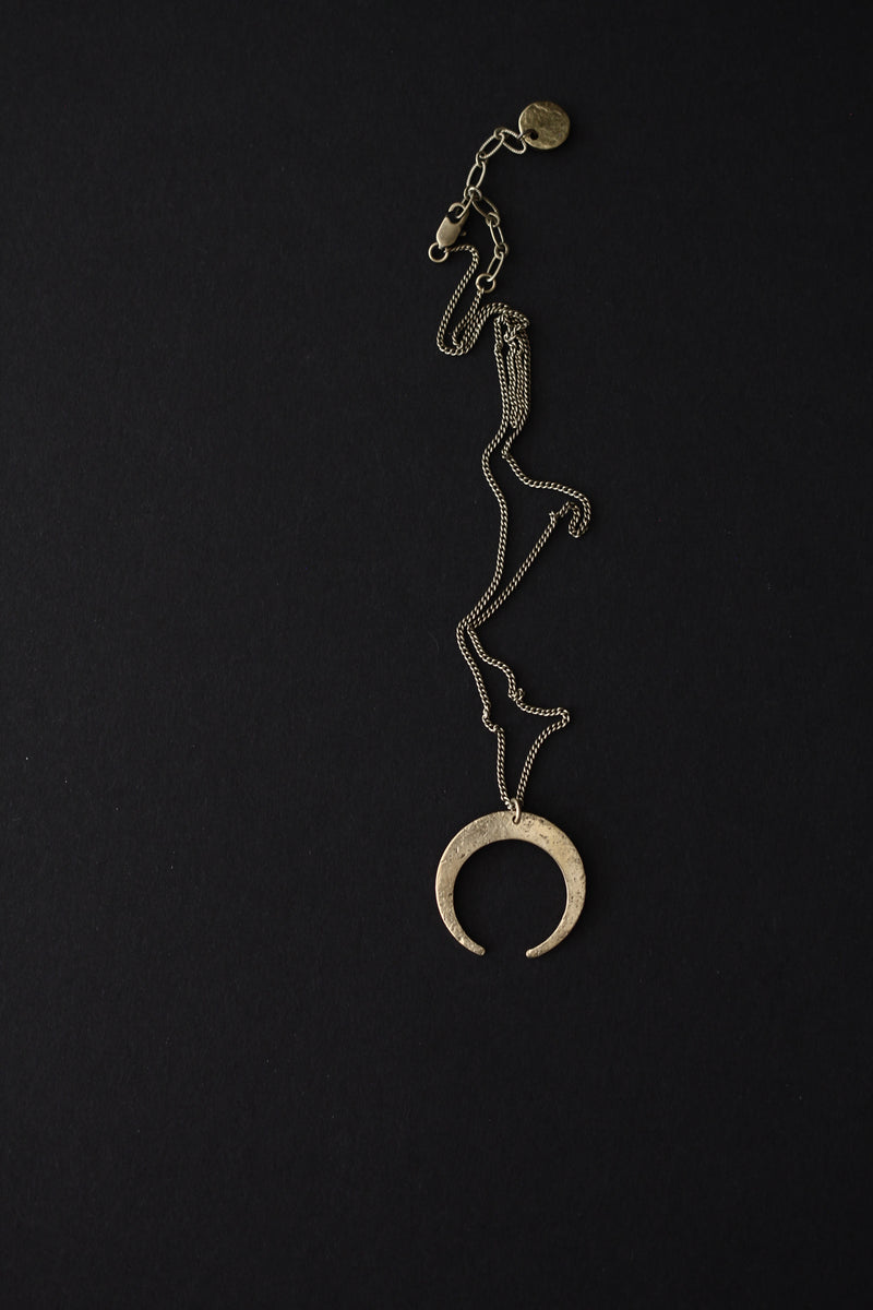 "Birds eye view showing the ""Arro"" necklace with it's textured, brass crescent moon pendant laid out on black background."