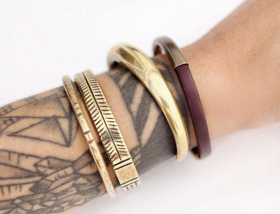 "Three brass bracelets and an ""Aster"" mahogany leather bracelet on model's wrist."