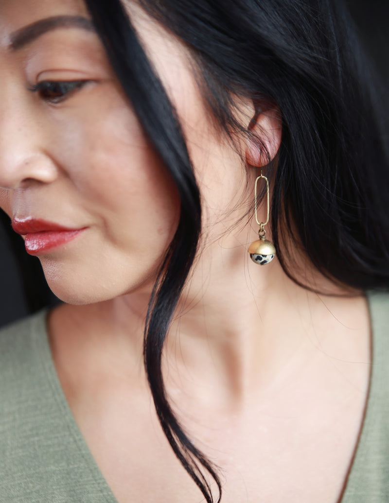 Modern woman modeling dalmatian jasper stone and brass earrings crafted by local Milwaukee Jewelry Designers, Cival Collective.