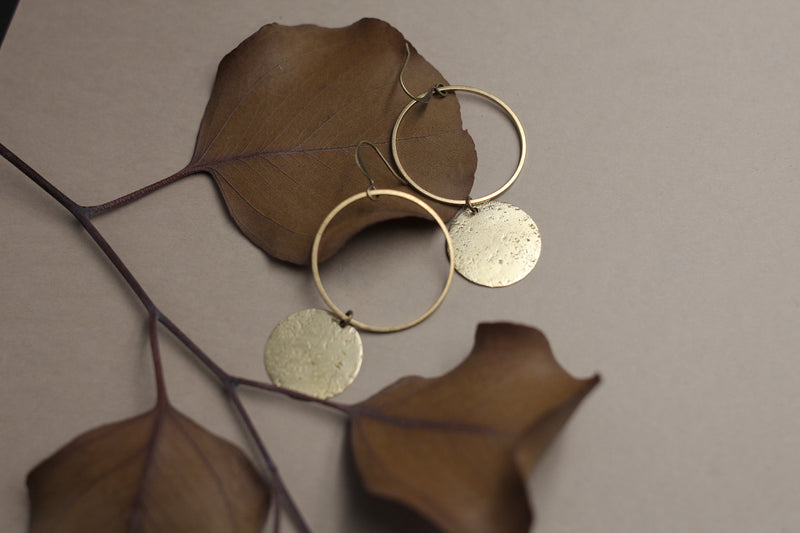 "Close up of ""Corrine"" earrings that consist of a large open brass ring on an ear wire and a smaller solid textured brass circle hanging below the open ring."