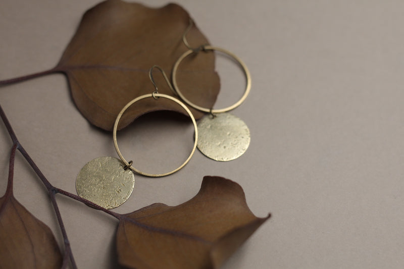 "CIVAL Collective's ""Corrine"" earrings that consist of a large open brass ring on an ear wire and a smaller solid textured brass circle hanging below the open ring."