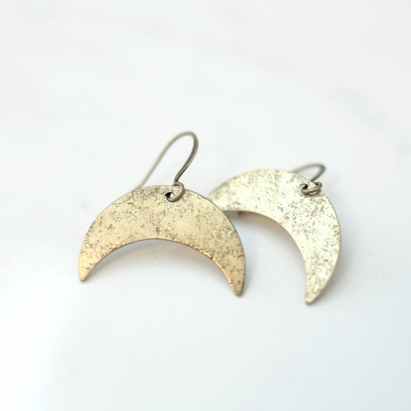 Small hand textured brass crescent moon earrings on french ear wire made by CIVAL in Milwaukee WI.