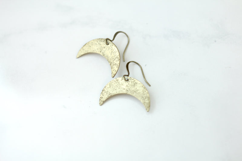 Close up of brass textured moon earrings by CIVAL Collective in Milwaukee WI.