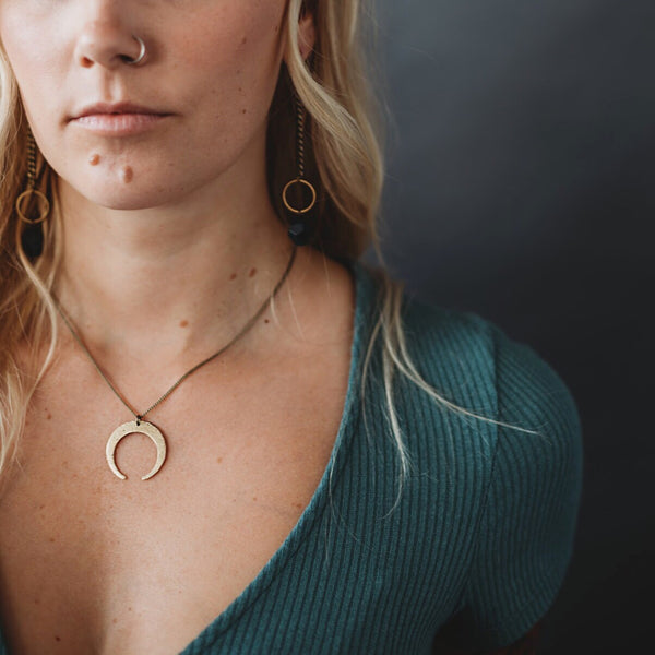 Model wearing short brass textured crescent moon necklace designed by CIVAL Collective.