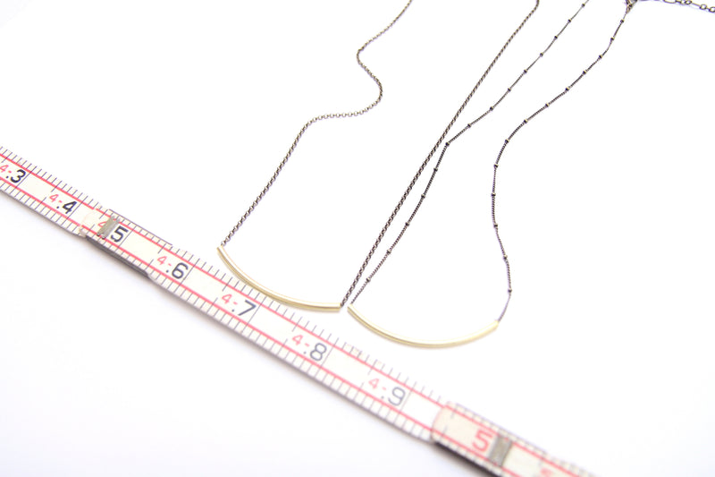 "Two ""London"" curved brass bar slider necklaces displayed next to a ruler to show the curved bar is 2 inches long."