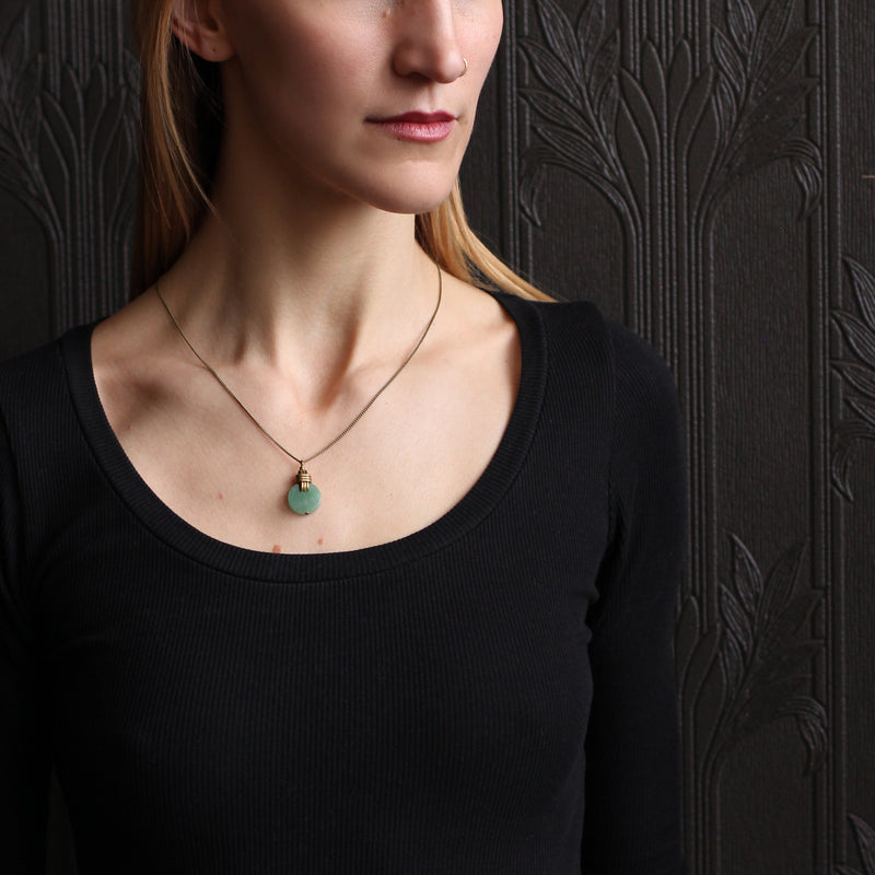 "A Cival Collective modern classic jade green necklace design is made with a green aventurine center stone and a vintage knot. Jackie is handmade in the US by a women owned and operated company in Milwaukee, WI. Jackie is 1/3"" sized coin shaped stone green aventurine stone combined with a simple brass knot design. This design is securely designed and finished with fine 1.5mm antique brass curb chain cut to 20"" inches & clasp closure."