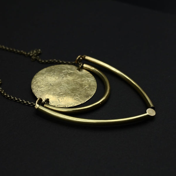 "Close up of ""Joan"" textured brass circle and brass tube shield necklace."