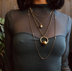 Three necklace layering set including two Dalmatian jasper necklaces & a brass sphere suspension necklace. Pictured on model from CIVAL Collective in Milwaukee WI.