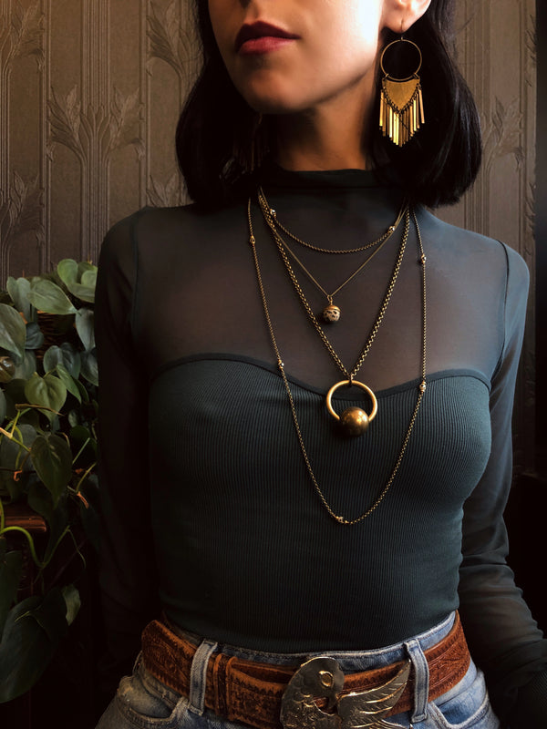 Three necklace layering set including two Dalmatian jasper necklaces & a brass sphere suspension necklace. Pictured on model from CIVAL Collective in Milwaukee WI. Also on model are the brass Dana earrings.