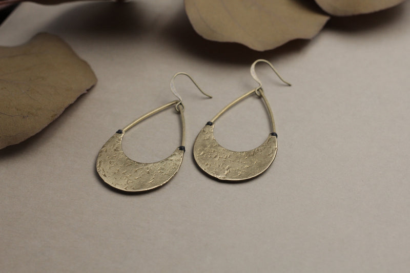 "Close up of ""Loral"" earrings with textured brass moons stitched onto open teardrop brass rings."