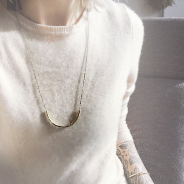 "CIVAL Collective model in white sweater wearing long ""Lydia"" bright brass arc necklace on rolo chain."