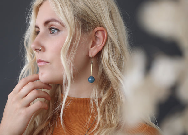 Introspective young woman wears the perfect gift, Blue angelite gem stone and brass earrings made by hand in Milwaukee Wisconsin by local jewelry designers Cival Collective.