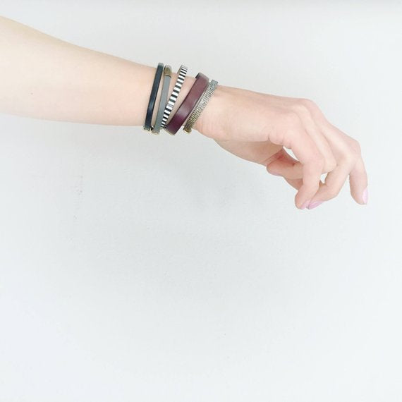 Model's arm layered with 5 different leather & fabric bracelets designed and made by Cival Collective.