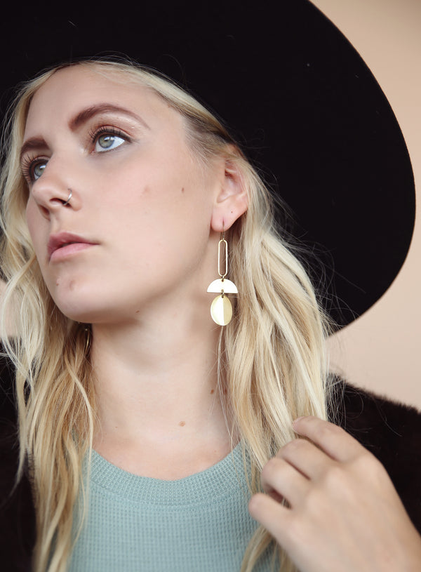 "Model in hat wearing CIVAL Collective's ""Myah"" brass earings that consist of and open oval, half moon, and solid oval stacked."