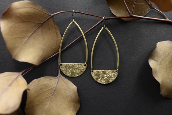 "CIVAL Collective's ""Nessa"" teardrop earrings with textured brass half moons on structured brass bars."