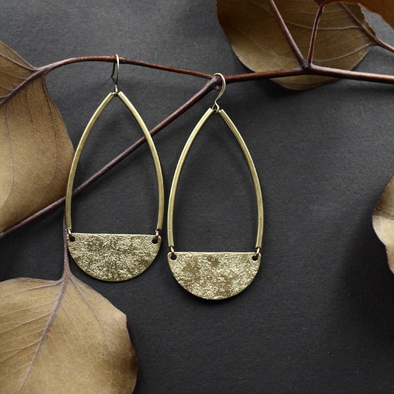 Textured half moon brass components hanging from structured bars to create airy lightweight teardrop shaped earrings.
