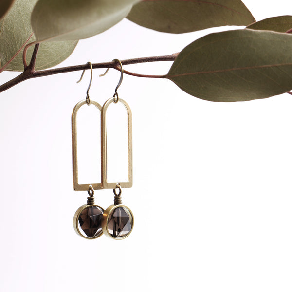 Pair of modern brass arch earrings with saddle set, faceted deep brown smokey quartz wire wrapped below arch.