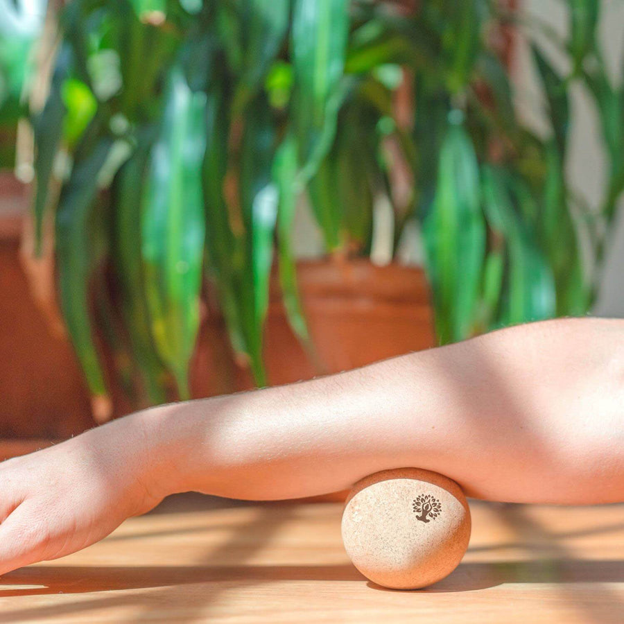 Massaging forearm with cork massage ball