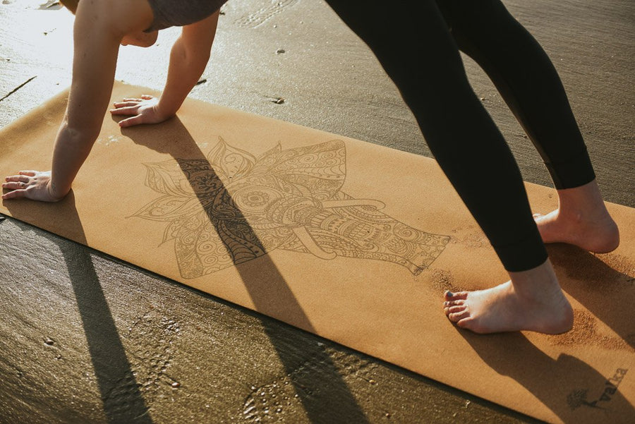 Yogini in downward dog on yoga mat on beach in NZ