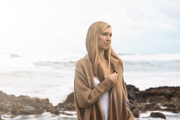 woman with long blonde hair standing at the beach wearing the tan Zeville sweater by illuminative.