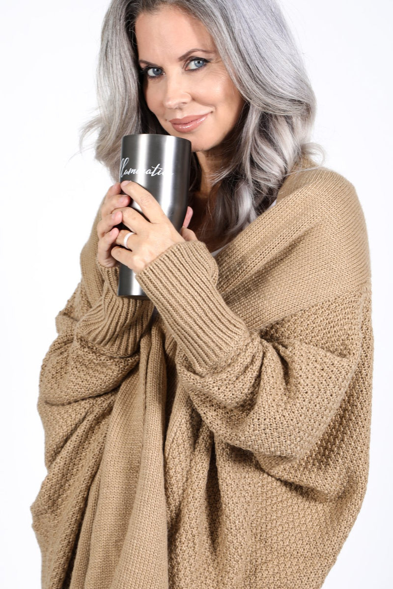 Model drinking from the illuminative tumbler and wearing the Zeville Cardigan in Camel.