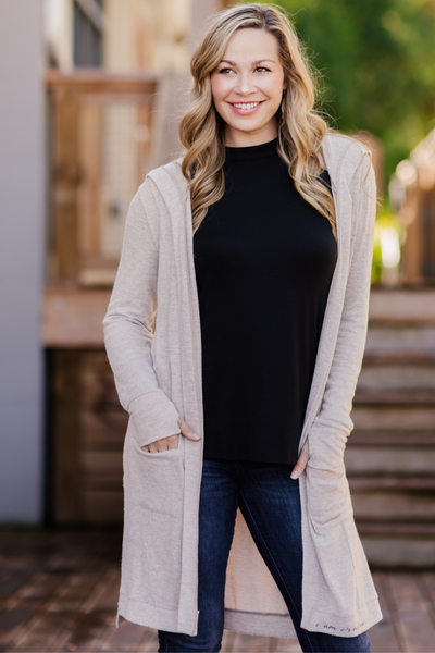 Model smiling, wearing Feny Cardigan, with hands in pockets.