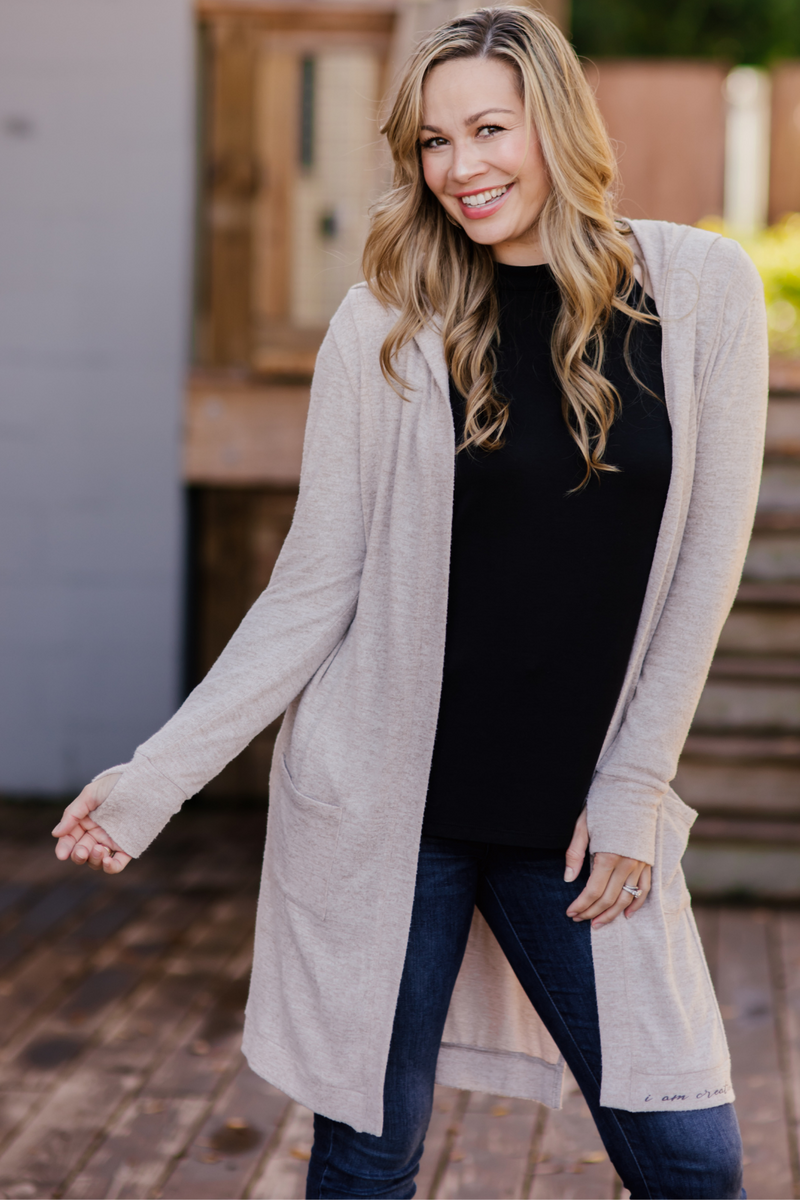 model smiling, wearing Feny Cardigan showing off the thumb holes with hands showing.