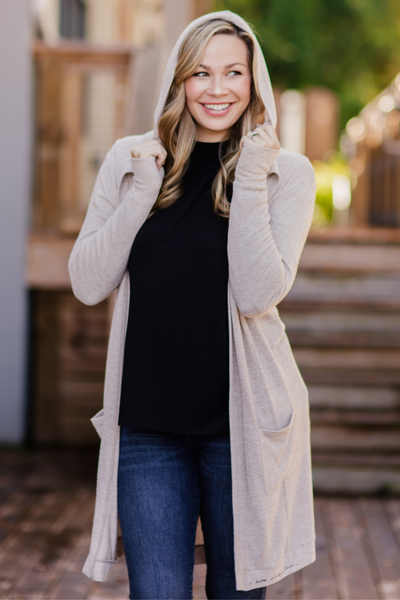Model smiling, wearing Feny Cardigan, holding hood which is up.