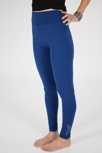 Photo of model from waist down wearing blue leggings with affirmation at left side by ankle.