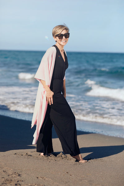 Model at the beach wearing the Lux Kimono in blush and the Kirigama Jumpsuit in black, by illuminative