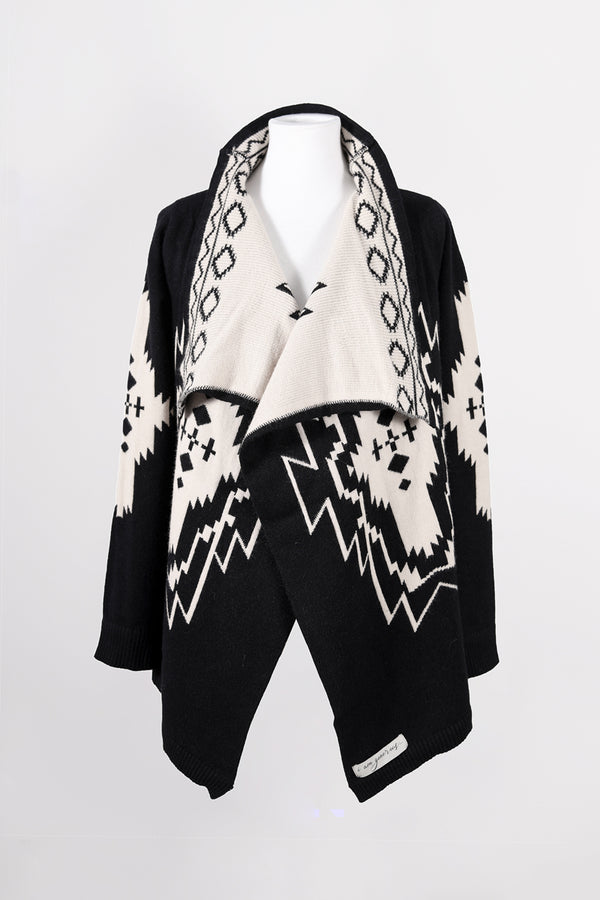 The best-selling Nani Cardigan by illuminative with black and cream geometric pattern, isolated view