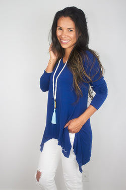 model wearing blue solas with white jeans, her hand is in one pocket of the jeans.