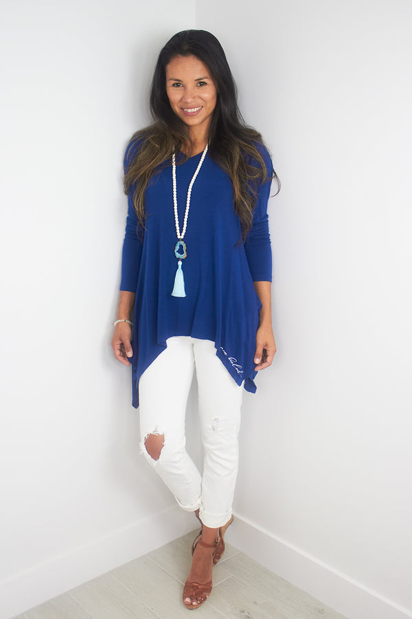 Model wearing blue Solas top with white distressed jeans and beaded necklace.